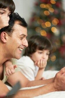 Przytulne zimowe dni. uśmiechnięty ojciec korzysta z cyfrowego tabletu, spędzając czas ze swoimi uroczymi małymi dziećmi, leżąc na łóżku w domu udekorowanym na boże narodzenie