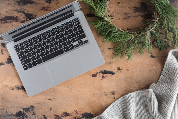 Przytulne zimowe tło z laptopem i świąteczny wieniec, szary ciepły pled z dzianiny, miejsce do pracy vintage. koncepcja stylu życia, widok z góry i płaskie lay