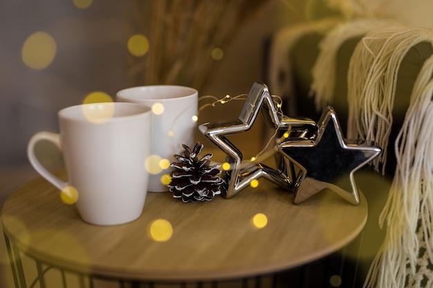 Przytulne zimowe tło - zbliżenie dwóch filiżanek herbaty, gwiazd i szyszki jodły na stole