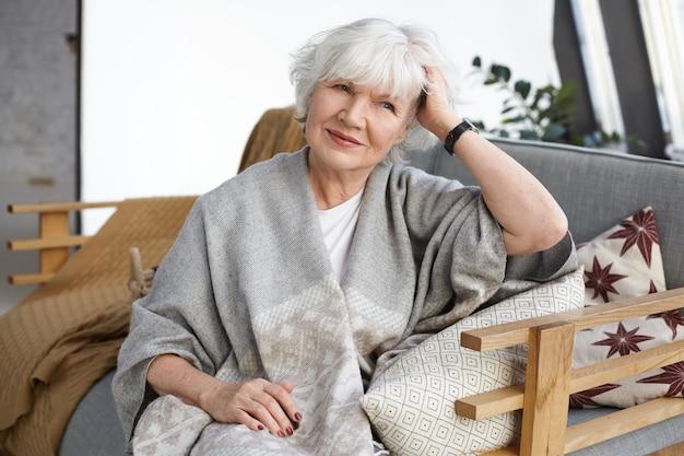 Przytulność, projektowanie wnętrz, wypoczynek, styl życia i koncepcja osób starszych. atrakcyjna elegancka dojrzała emerytka ze zmarszczkami i siwymi włosami, relaksując się na kanapie w swoim wiejskim domu, uśmiechając się