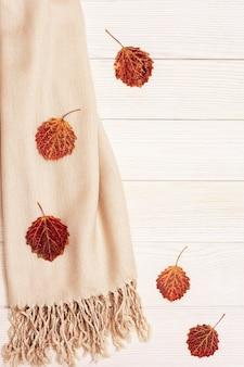 Przytulny beżowy szalik i naturalne liście osiki.