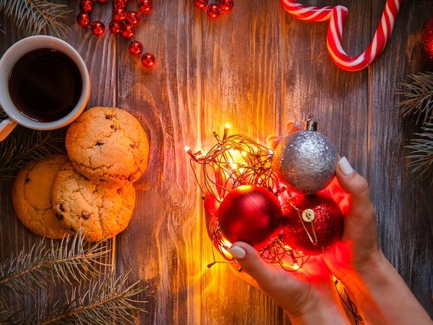 Przytulny ciepły świąteczny wystrój na drewnianym tle. świąteczny nastrój i świąteczny nastrój stworzyły ręce kobiety trzymające bajkowe światełka i błyszczące kule. filiżanka kawy ciasteczka z kawałkami czekolady i trzciny cukrowej.