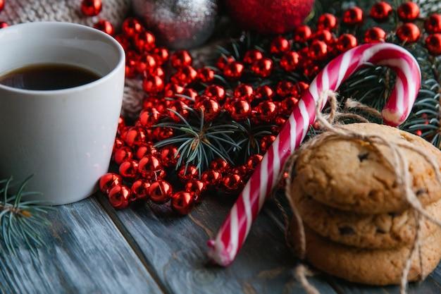 Przytulny ciepły świąteczny wystrój na drewnianym tle. świąteczny nastrój i świąteczny nastrój. sweter z dzianiny i czerwony sznureczek z kubkiem gorącej kawy i ciasteczkami czekoladowymi.