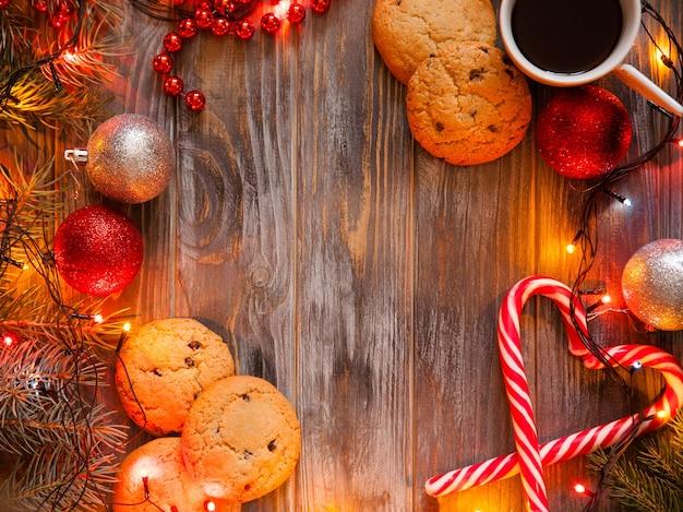 Przytulny ciepły świąteczny wystrój na drewnianym tle. świąteczny nastrój i świąteczny nastrój tworzony przez bajkowe światełka i błyszczące kule. filiżanka kawy ciasteczka czekoladowe i trzciny cukrowej w kształcie serca.