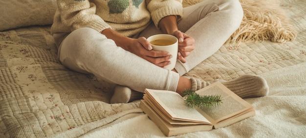 Przytulny dom. piękna kobieta czyta książkę na łóżku. dzień dobry z herbatą i książką. bardzo młoda kobieta relaksujący. pojęcie czytania