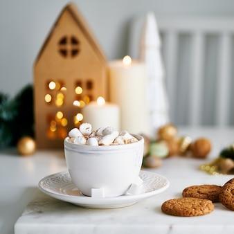 Przytulny domowy świąteczny klimat, świąteczny dom wakacyjny. domowe ciasteczka z frytkami i kubek gorącej czekolady. jasnoszarym tle. dom z papieru kraft. selektywna ostrość, rozmyte tło