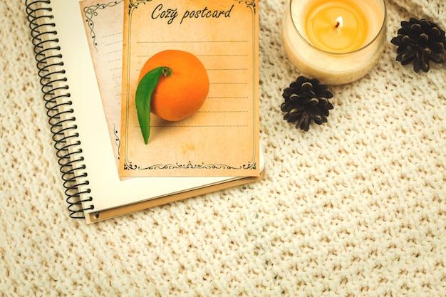 Przytulny domowy szablon koncepcji komfortu zimowego, tło z dzianinowych swetrów, książek i mandarynek, kopia zdjęcia kompozycji przestrzeni