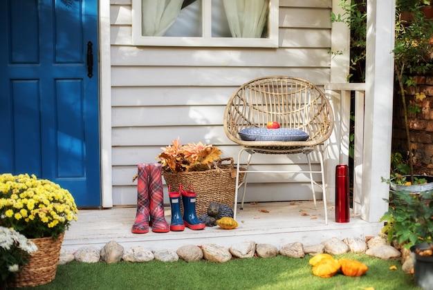 Przytulny jesienny taras z krzesłem, pledem, gumowymi butami, koszami z chryzantemami i dyniami.