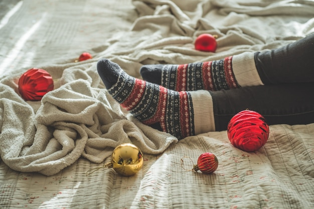 Przytulny jesienny zimowy wieczór, ciepłe wełniane skarpety. kobieta leży na białym kudłatym kocu z zabawkami świątecznymi