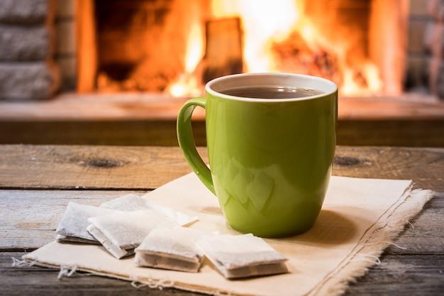 Przytulny kominek i filiżanka herbaty, w wiejskim domu, zimowe wakacje.