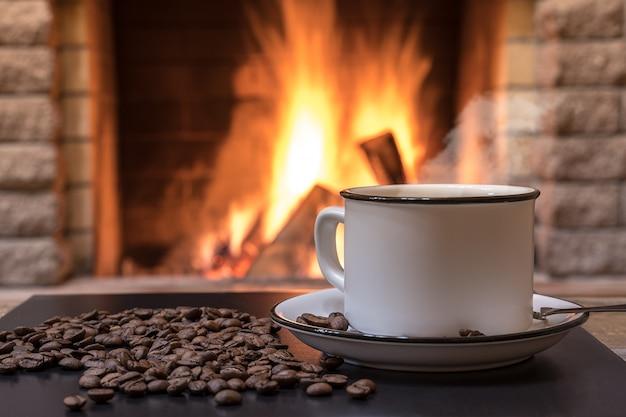 Przytulny kominek i filiżanka kawy, ziarna kawy, w wiejskim domu, zimowe wakacje.