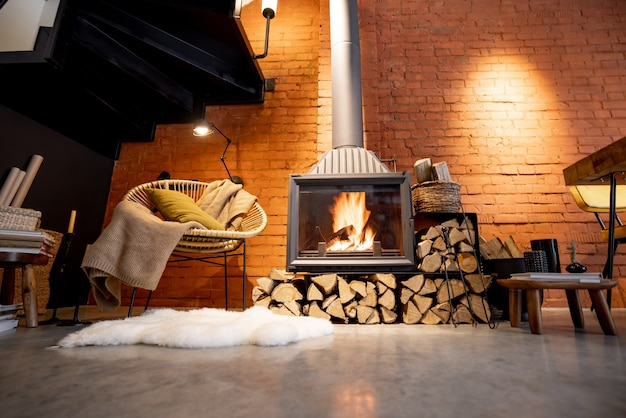 Przytulny kominek z drewnem opałowym w stylu loftowym wnętrze domu z tłem ceglanego muru, płonący ogień w kominku, domowa przytulność w zimie