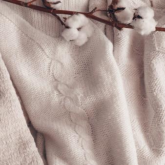 Przytulny kwiat bawełny. bawełna z ciepłym swetrem. kompozycja twórcza martwa natura. modne jesienne tło z suszoną bawełną.