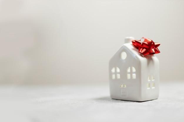Przytulny model małego domu z czerwoną wstążką