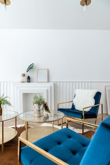 Przytulny narożnik salonu ze złotym i niebieskim aksamitnym fotelem z tkaniny i złotym lustrzanym stolikiem kawowym w nowoczesnym klasycznym stylu z sceną naturalnego światła