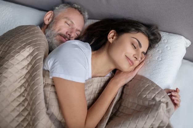 Przytulny nastrój. mężczyzna i kobieta śpią razem w łóżku