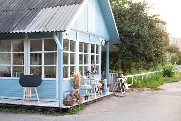 Przytulny niebieski dom z pięknym ogrodem w lecie. piękny dom wiejski z wiklinowymi koszami i zielonymi roślinami na tarasie.