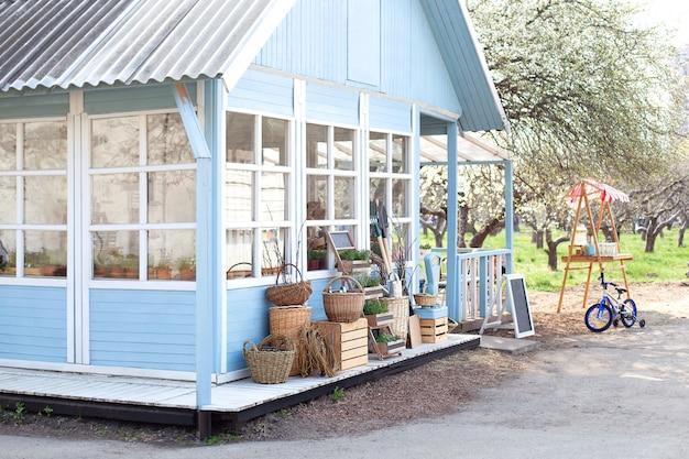 Przytulny niebieski dom z pięknym ogrodem w słoneczny dzień. styl rustykalny. koncepcja jesień. dom na wsi. piękny dom wiejski z wiklinowymi koszami ze zbiorami. podwórko domu rolnika.