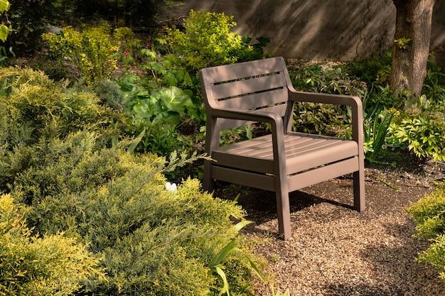 Przytulny plastikowy fotel w magicznym ogrodzie wśród zielonych jałowców w cieniu tajemniczych drzew ogrodowych
