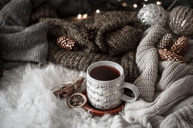 Przytulny poranek bożonarodzeniowy z filiżanką herbaty w łóżku. martwa natura ze swetrami. parze filiżankę gorącej kawy, herbaty. koncepcja bożego narodzenia.