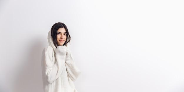 Przytulny. portret pięknej kobiety brunetka w wygodny miękki długi rękaw na białym tle na białej ścianie. komfort w domu, emocje, wyraz twarzy, koncepcja zimowego nastroju. copyspace.