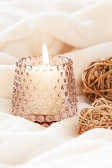 Przytulny skandynawski hygge z płonącymi świecami i brązowymi naturalnymi dekoracjami na białym miękkim kocu.
