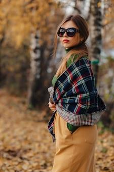 Przytulny stylowy młoda dziewczyna spacer w jesień kolorowy park w okulary
