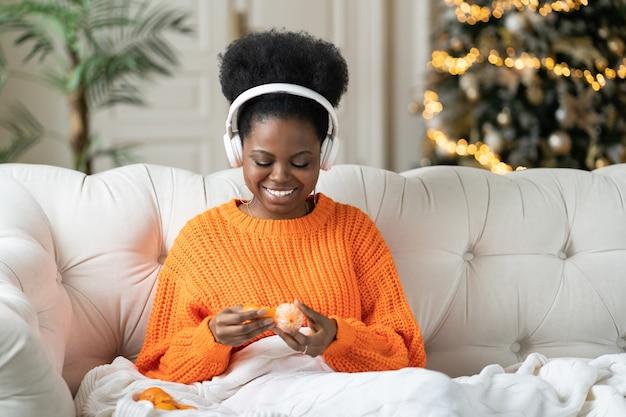 Przytulny świąteczny lub noworoczny poranek w domu szczęśliwa młoda afrykańska kobieta słucha muzyki je mandarynki w łóżku