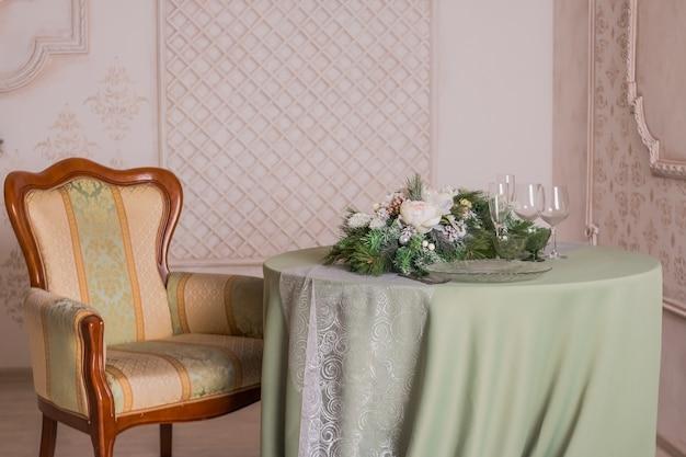 Przytulny świąteczny stół z płonącymi świecami, kieliszkami i talerzami. romantyczna kolacja dla dwóch osób. duży talerz z daniem głównym, szampanem w okularach. plaid z tyłu krzesła. widok z góry.