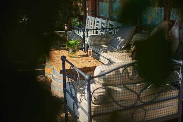 Przytulny taras z sofami do odpoczynku, kieliszek szampana na drewnianym stole.