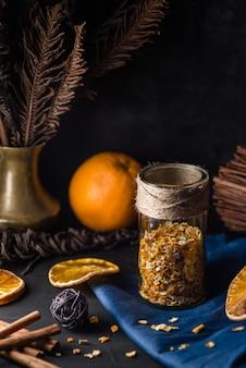 Przytulny urlop zimowy z skórką pomarańczową i skórką pikantnych składników do pieczenia. boże narodzenie martwa natura z suszonymi plasterkami pomarańczy i cynamonem