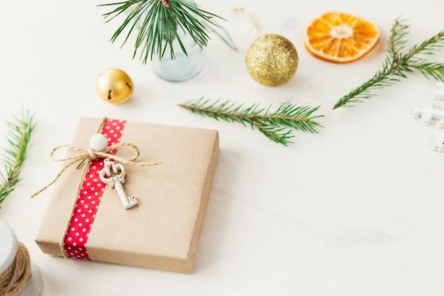 Przytulny vintage stonowanych ferii zimowych boże narodzenie skład z pudełka na prezenty i kulki, szyszki sosnowe drewniane tła. stylizowana fotografia do wpisów na blogu. płaski widok z góry.