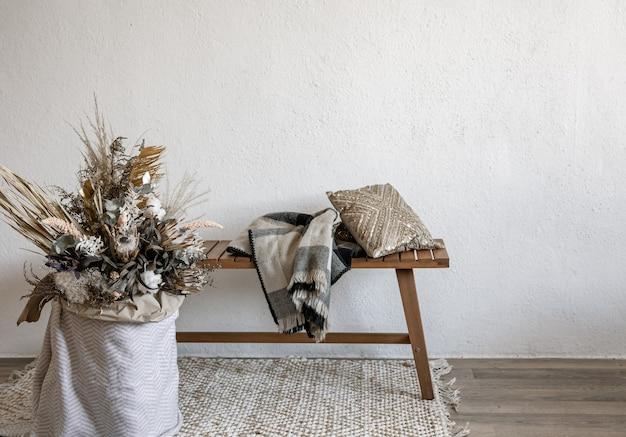 Przytulny wystrój wnętrz w stylu skandynawskim z elementami dekoracyjnymi i modną kompozycją suszonych kwiatów.