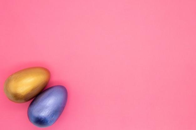 Przytulny zestaw niebieskie i srebrne pisanki na różowym tle. widok z góry