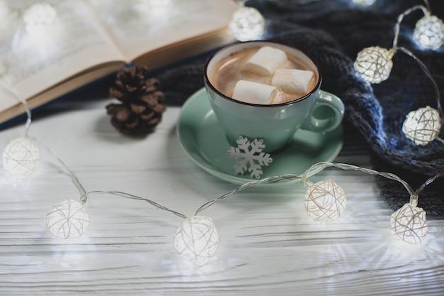 Przytulny zimowy dom. filiżanka kakao z piankami, ciepły sweter z dzianiny, otwarta książka, świąteczna girlanda na białym drewnianym stole. atmosfera miłego wieczoru do czytania.