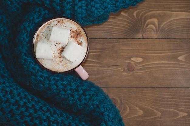 Przytulny zimowy dom. filiżanka kakao z piankami i niebieski szal z dzianiny na brązowym drewnianym stole. miejsce na tekst.