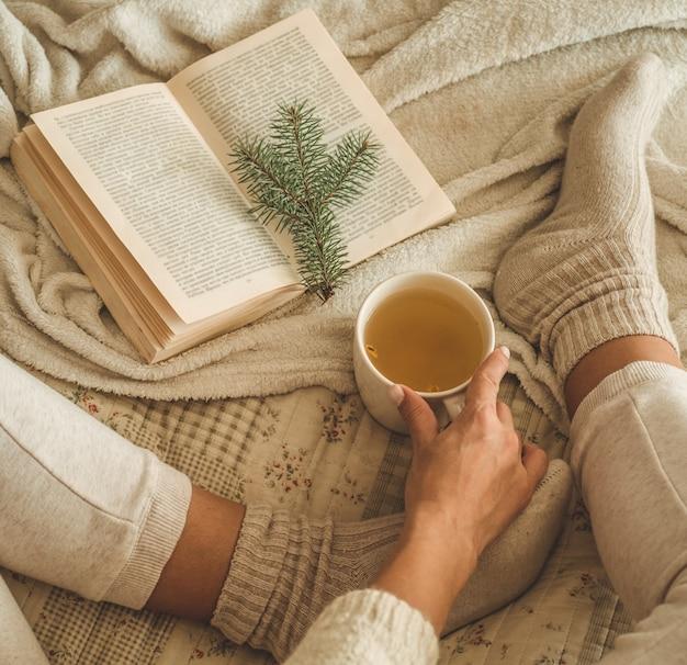 Przytulny zimowy wieczór, ciepłe wełniane skarpety. kobieta leży nogi na białym kudłatym kocu i czytając książkę. przytulna scena wypoczynkowa. tekst w książce jest nieczytelny. kobieta relaks w domu. wygodny styl życia.
