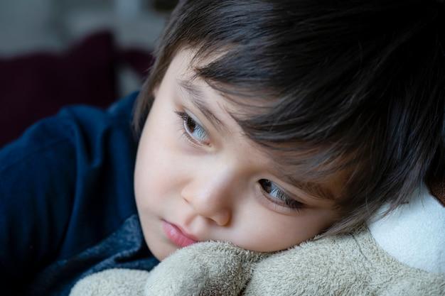 Przytulona twarz smutnego dzieciaka leżącego z głową na misiu, szczera, krótka samotna głowa dziecka na swojej zabawce spoglądająca głęboko w zamyśleniu, snape zastrzelił małego chłopca siedzącego samotnie.
