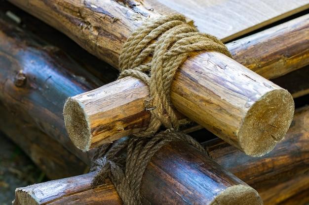 Przywiąż linę do drewna. zawiąż sznurek na patyku. zawiąż linę na drewnie.