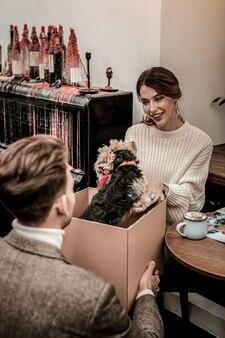 Przywiezienie zwierzaka. kobieta czuje się szczęśliwa otrzymując pudełko ze szczeniakiem