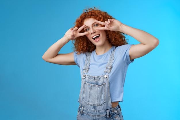 Przywitaj cheeze, lato. wesoły uroczy zabawny charyzmatyczny rudy ładna dziewczyna kręcone fryzury pokaż język pokój zwycięstwo gest oczy przechylić głowę radosny naśladując zabawną postawę szczęśliwe emocje.