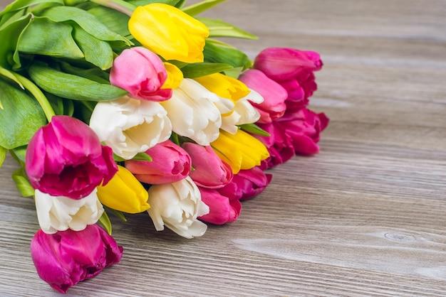 Przywitaj wiosnę koncepcja. zbliżenie: piękny wielobarwny bukiet pięknych tulipanów na szarym drewnianym stole kopia przestrzeń