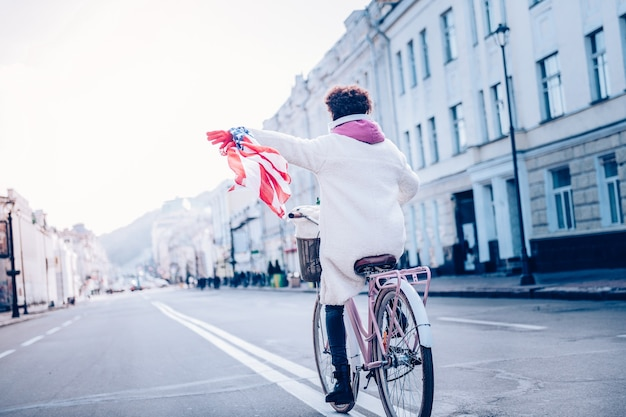 Przywódca grupy. zachwycona kobieta jeżdżąca na rowerze, podziwiając widoki na miasto