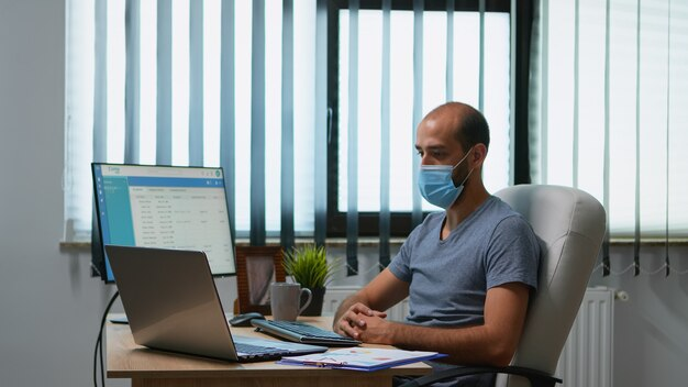 Przywódca z maseczką medyczną rozmawiający z kolegami za pomocą czatu wideo online podczas covid-19. freelancer pracujący w nowym normalnym biurze biurowym rozmawiając o wirtualnej konferencji, spotkaniu.