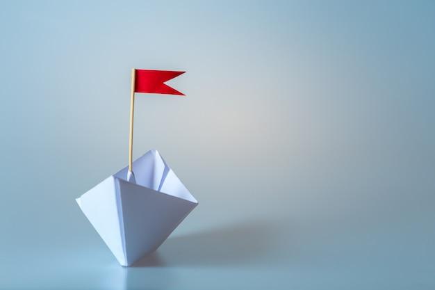 Przywódctwo pojęcie używać papierowego statek z czerwoną flaga na błękitnym tle
