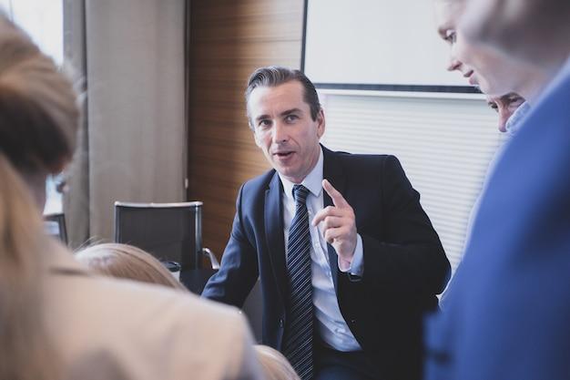 Przywództwo i komunikacja. mowa biznesowa. przystojny dorosły mężczyzna w garniturze rozmawia ze swoimi kolegami - grupa ludzi przy stole konferencyjnym