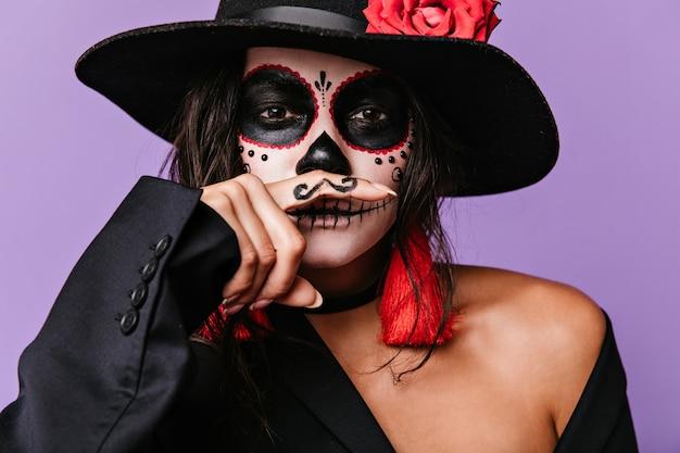 Psotna brązowooka dziewczyna ze zdobieniem twarzy bawi się, przykładając do ust pomalowane wąsy. zdjęcie stylowej kobiety w czarnym stroju z czerwonymi detalami.