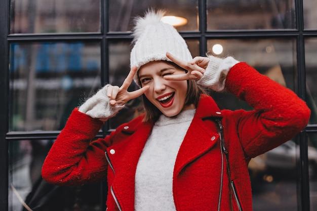 Psotna krótkowłosa dziewczyna w ciepłym kapeluszu i czerwonym płaszczu mruga. ujęcie kobiety z czerwoną szminką przedstawiające znaki pokoju przed oknem.