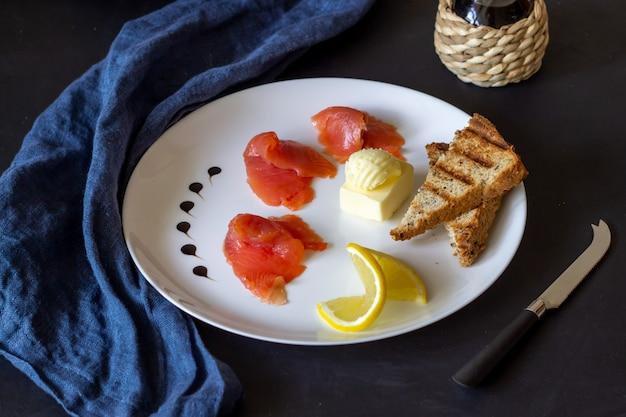 Pstrąg, masło i chleb na talerzu. ciemne tło