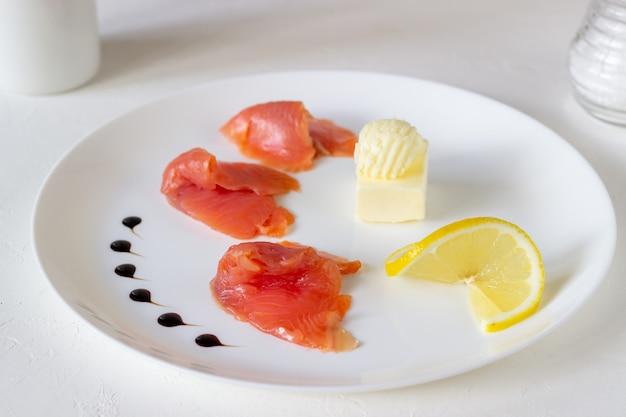 Pstrąg, masło i cytryna na talerzu. białe tło